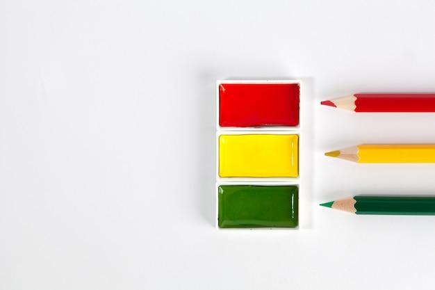 Acuarelas rojas, amarillas y verdes y lápices de colores afilados.