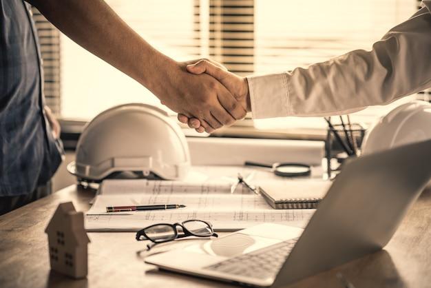 Acuerdo de apretón de manos de los clientes con el contratista para la construcción de casas