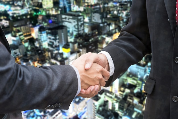 Acuerdo de apretón de manos del empresario con asociación en el fondo del edificio de luz brillante
