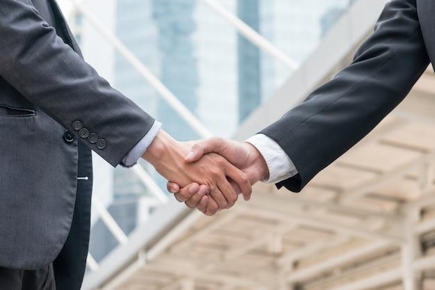 Acuerdo de apretón de manos de empresario con sociedad en urbanismo.