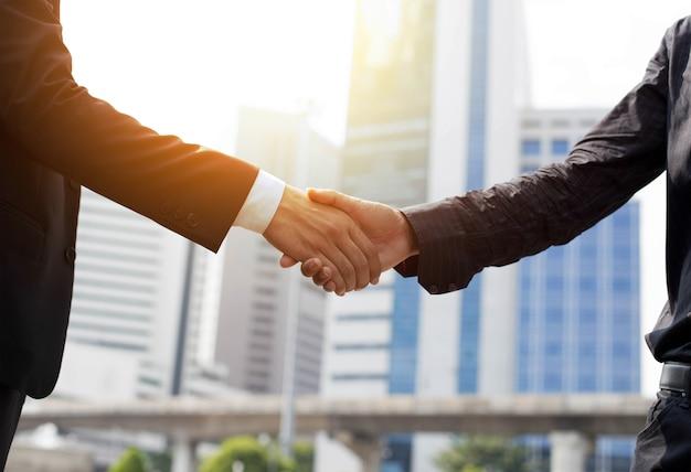 Acuerdo de negocios mano temblando delante del edificio moderno