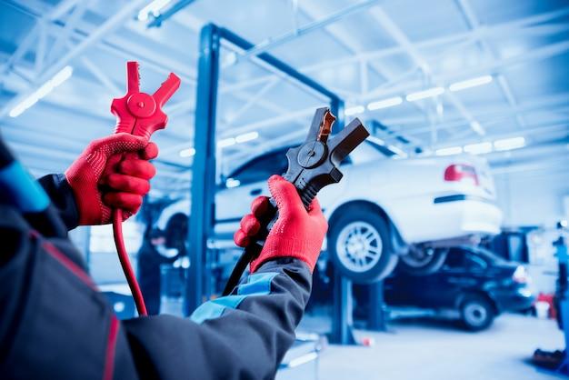 Acumulador de carga. manos y terminales. reparación de autos.