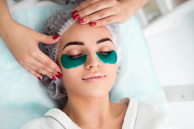 Acupresión, masaje en las sienes, escamas verdes de colágeno. procedimiento cosmético, el rostro de la mujer con escamas verdes debajo de los ojos.