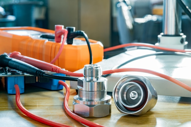 Adaptador coaxial microondas 7 conector 16 din macho a n hembra y multímetro electrónico digital en mesa de taller. componente de alta frecuencia con revestimiento metálico