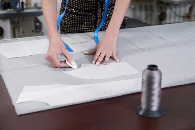 Adaptar la línea de dibujo en la tela con tiza en el taller de estudio