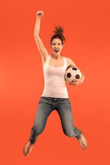 Adelante a la victoria. la joven como futbolista saltando y pateando la pelota en el estudio sobre un fondo rojo. aficionado al fútbol y concepto de campeonato mundial. conceptos de emociones humanas