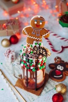 Aderezo de batido de navidad con hombre de jengibre, crema batida y chocolate derretido en la mesa del partido