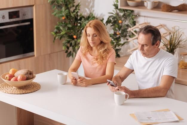 Adicto a la pareja involucrada curiosa sentada en casa y usando teléfonos inteligentes mientras se ignoran mutuamente