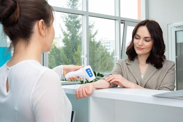 El administrador mide la temperatura de la mujer con un termómetro electrónico.