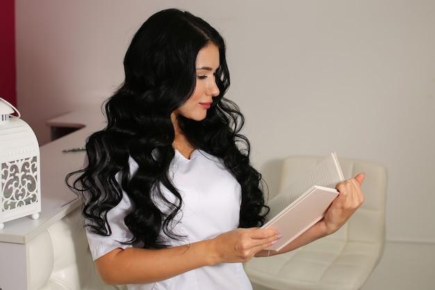 Administrador de mujer hermosa en uniforme blanco lee notas de escritura de bloc de notas.