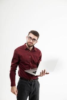 Administrador del sistema con una computadora portátil contra el fondo blanco.