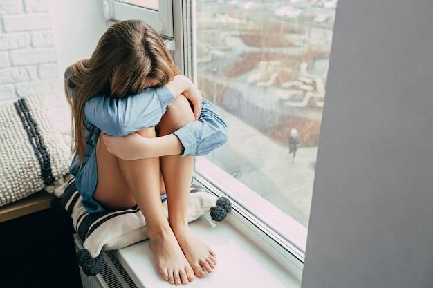 Adolescente abrazando las rodillas y sentado en el alféizar de la ventana