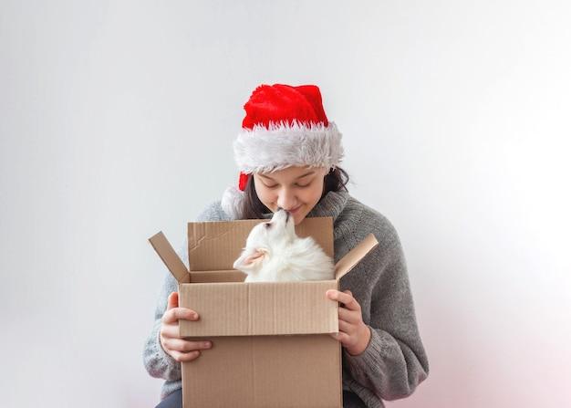 Una adolescente abre una caja de cartón y hay un perrito pomerania.