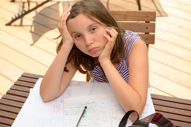 Adolescente aburrida está haciendo su tarea
