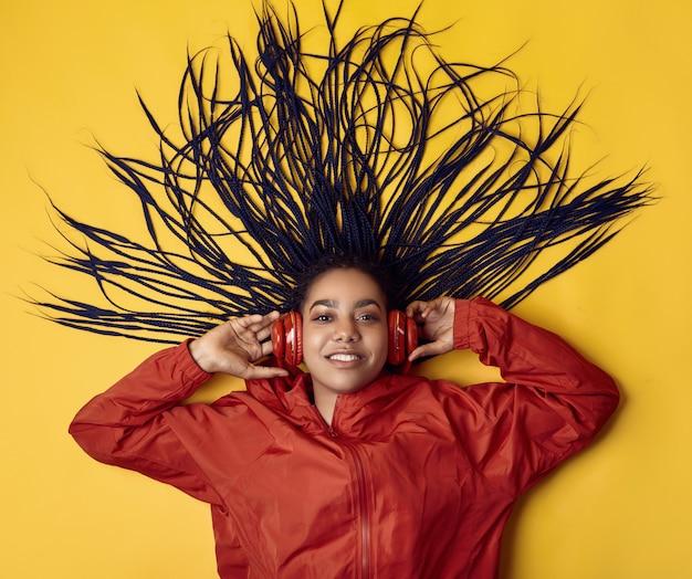 Adolescente africana con rastas en cazadora roja escuchando música