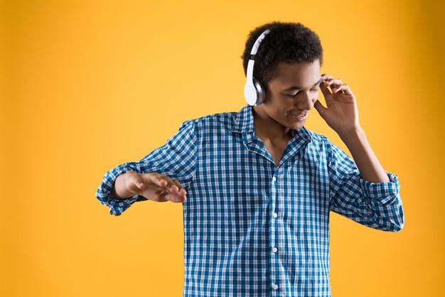 Adolescente afro en auriculares está bailando.
