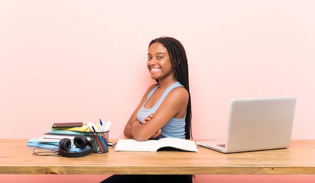 Adolescente afroamericana estudiante chica con cabello largo trenzado en su lugar de trabajo con los brazos cruzados y mirando hacia adelante