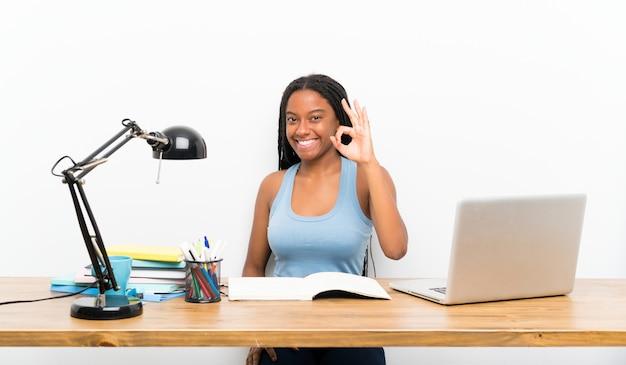 Adolescente afroamericana estudiante chica con cabello largo y trenzado en su lugar de trabajo que muestra signo bien con los dedos