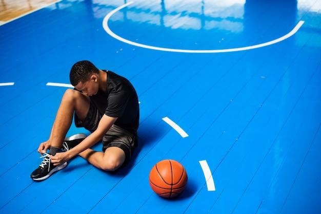 Adolescente afroamericano atar sus cordones de zapatos en una cancha de baloncesto