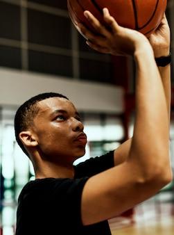 Adolescente afroamericano concentrado en jugar baloncesto