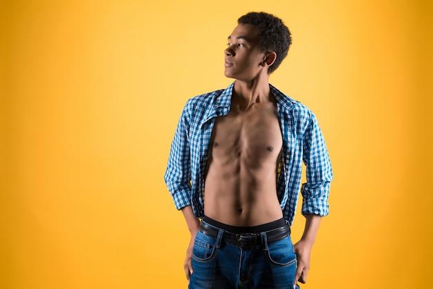Adolescente afroamericano delgado muestra torso desnudo.