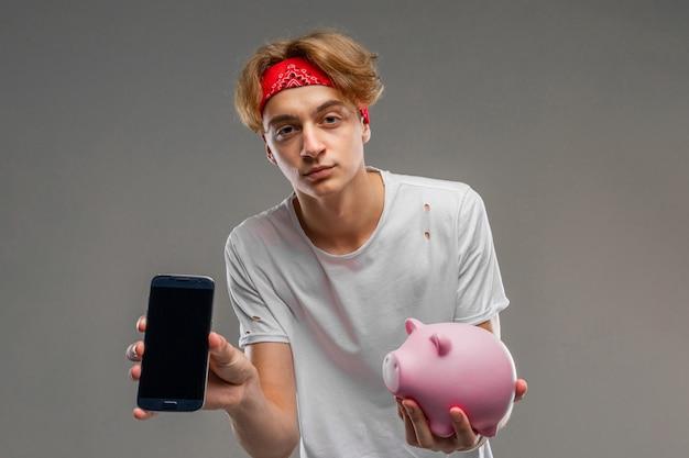 Adolescente con alcancía posando contra gris, joven con una camiseta ligera contra un fondo de pared gris