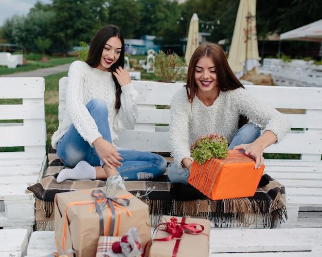 Adolescente alegre cogiendo un regalo naranja