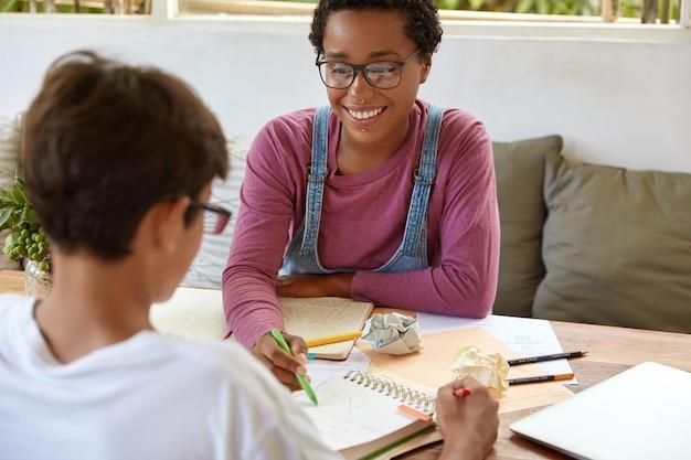 Adolescente alegre intenta explicarle el material a su hermano menor que se sienta frente a la cámara