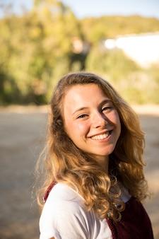Adolescente alegre sonriendo en el parque