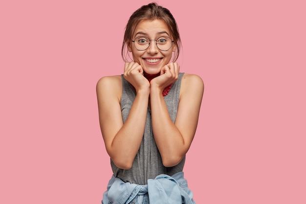 Adolescente alegre tiene una sonrisa con dientes, sostiene la barbilla con ambas manos, mira con expresión feliz directamente a la cámara