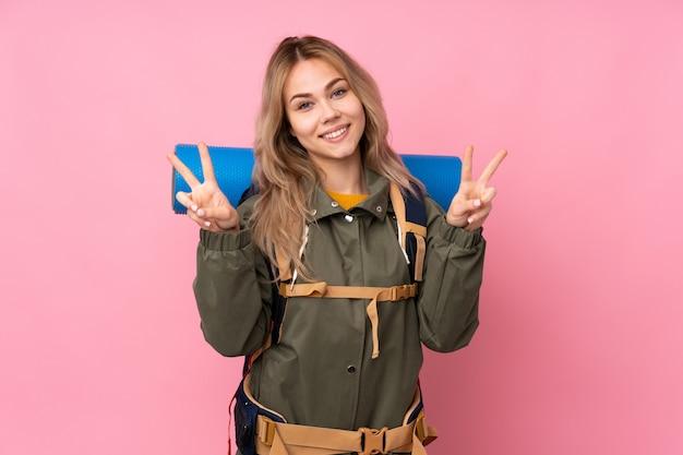 Adolescente alpinista con una mochila grande en la pared rosa que muestra el signo de la victoria con ambas manos