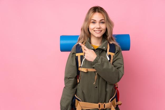 Adolescente alpinista con una mochila grande en la pared rosa que señala a un lado para presentar un producto