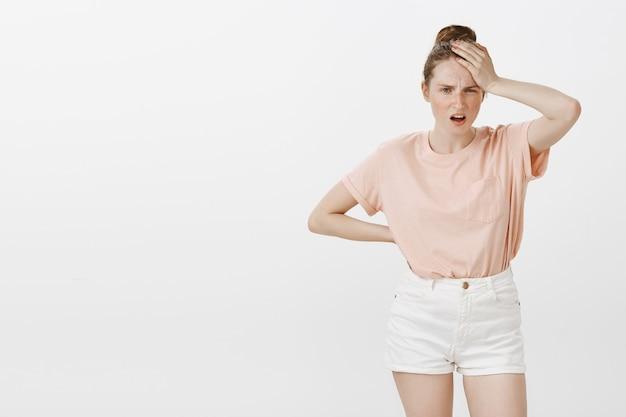 Adolescente angustiada y preocupada posando contra la pared blanca
