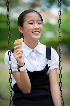 Adolescente asiática comiendo helado con cara de felicidad en el parque verde