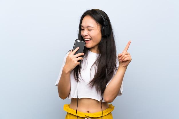 Adolescente asiática escuchando música sobre el canto de la pared azul aislado