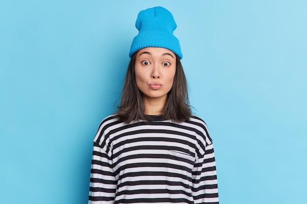 Adolescente asiática de moda con cabello oscuro mantiene los labios doblados