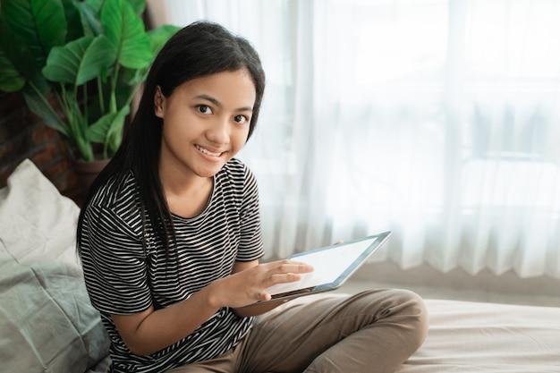 Adolescente asiática con tableta móvil