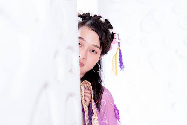 Adolescente asiática con vestidos tradicionales chinos asomándose detrás de la pared blanca