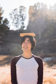 Adolescente asiático divirtiéndose con el libro