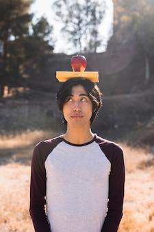 Adolescente asiático con libro y manzana en la cabeza