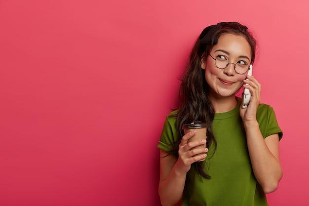 Adolescente asiático pensativo y contento recuerda recuerdos agradables durante una conversación telefónica, toma café y habla por teléfono móvil, se concentra a un lado, se viste con ropa informal, se siente aliviado y relajado