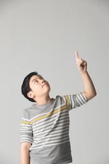 El adolescente asiático del preadolescente destaca para arriba sobre fondo gris.