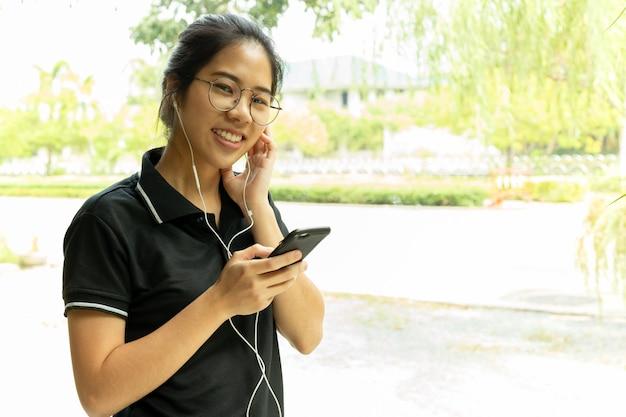 Adolescente asiático con los vidrios que escuchan en el teléfono celular que mira la cámara.