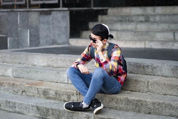 Adolescente atractivo en camisa a cuadros, jeans, gafas de sol y gorra de béisbol sentado en un campus universitario en las escaleras esperando a alguien o algo. estilo de vida de la tecnología de la educación. chico de moda