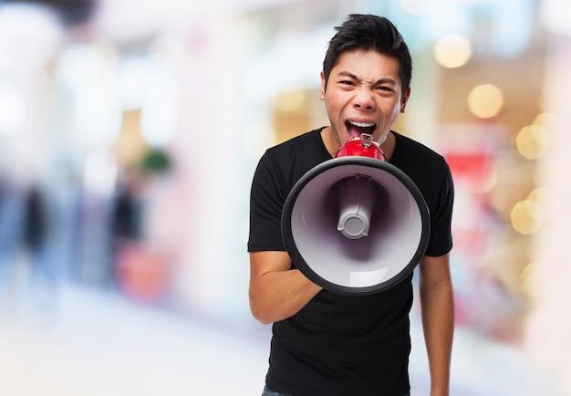 Adolescente atractivo usando un megáfono
