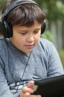 Adolescente en auriculares al aire libre escuchando música o viendo videos en una tableta
