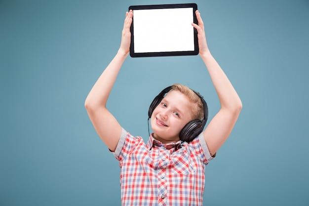Adolescente con auriculares muestra pantalla de tableta, foto con espacio para texto
