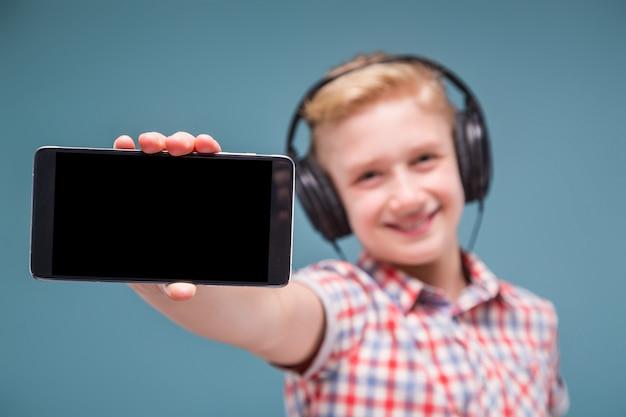 Adolescente con auriculares muestra la pantalla del teléfono inteligente
