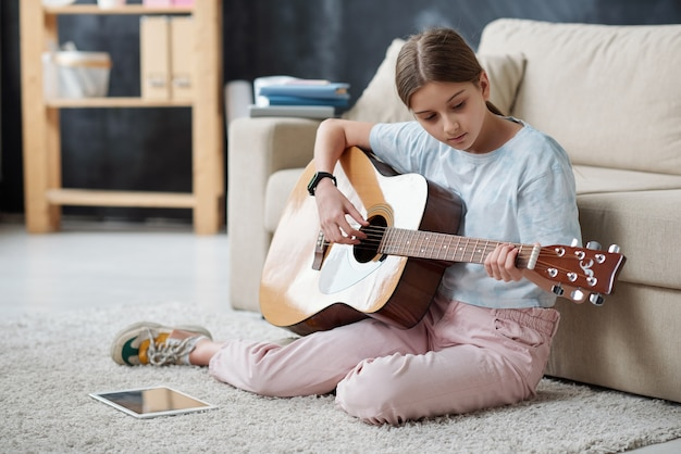 Adolescente autodidacta sentada en una alfombra y usando videos instructivos en tableta mientras toca la guitarra