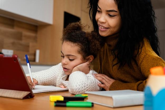 Adolescente ayudando a hermanita durante la escuela en línea con tableta